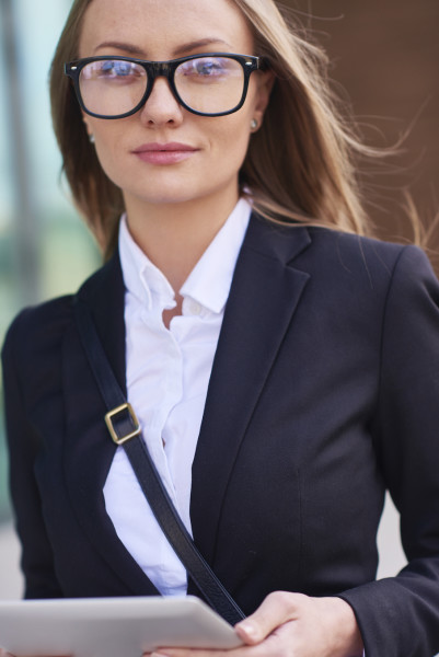 Young businesswoman in glasses looking at camera